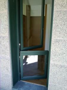 Puerta de aluminio tipo postigo, con apertura superior e inferior.